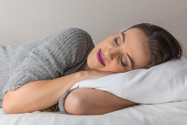 Belle femme dormant sur un oreiller confortable au lit à la maison