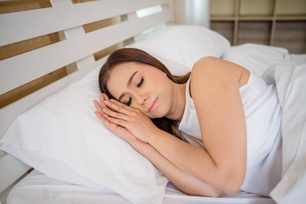 Belle femme dort dans la chambre à coucher, allongée sur le lit
