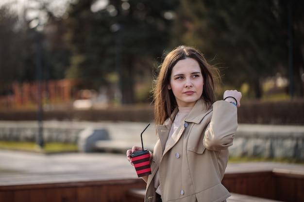 Belle femme avec du café à la main se promène par temps ensoleillé autour de la ville