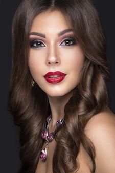 Belle femme avec du maquillage arabe, des lèvres rouges et des boucles