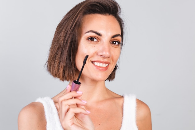 Belle femme avec du maquillage tient une brosse à mascara noire sur un mur gris, concept de beauté