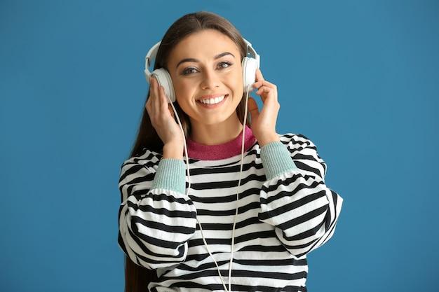 Belle femme écoutant de la musique sur la couleur