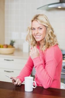 Belle femme écoutant de la musique dans la cuisine