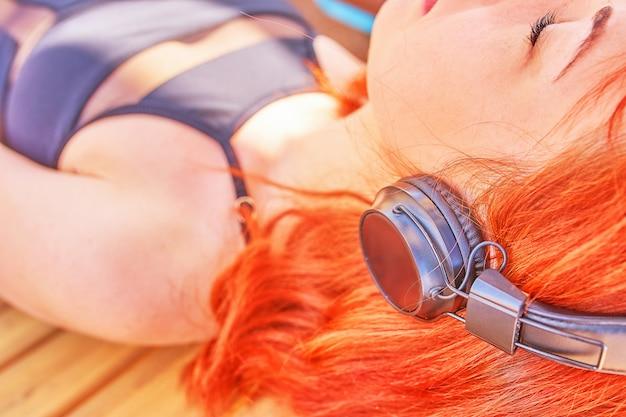 Belle femme écoutant de la musique sur la plage.