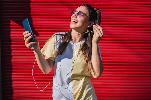 Belle femme écoutant de la musique avec son smartphone sur fond rouge.