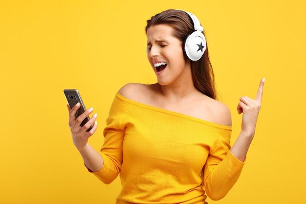 Belle Femme écoutant De La Musique Sur Téléphone Mobile Sur Jaune Photo Premium