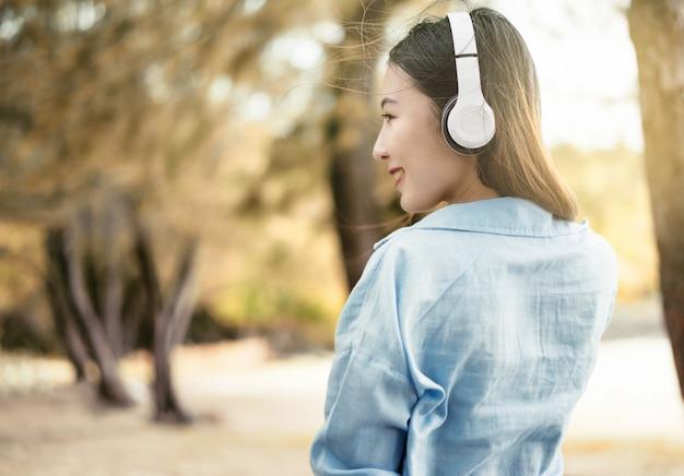 Belle femme écoute de la musique dans le jardin. détendez-vous avec de la musique en vacances.