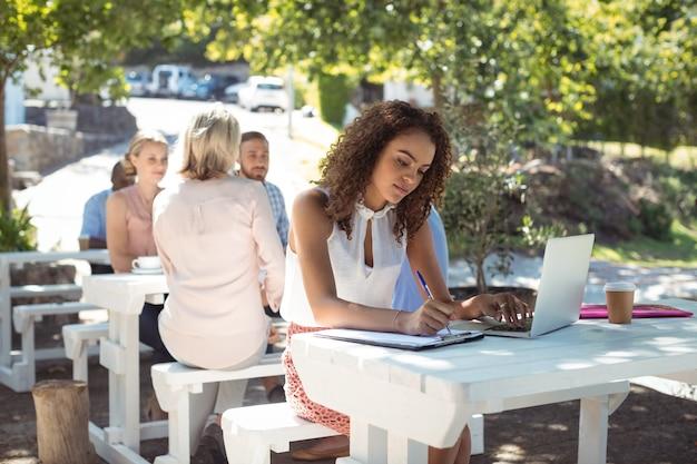 Belle femme écrivant sur le presse-papiers tout en utilisant un ordinateur portable