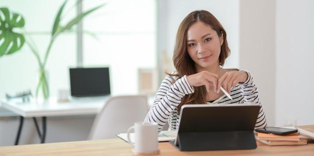 Belle femme édite son projet avec tablette et souriant