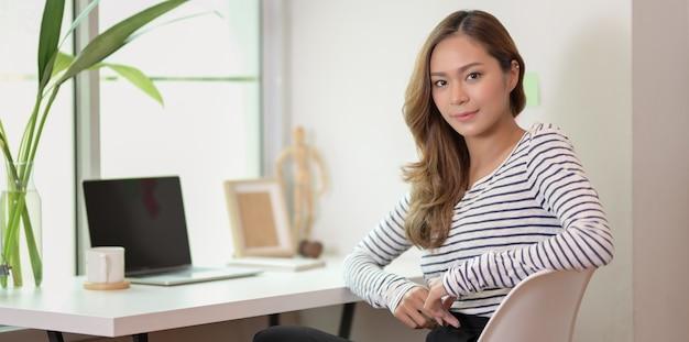 Belle femme éditer son projet avec un ordinateur portable et à la recherche