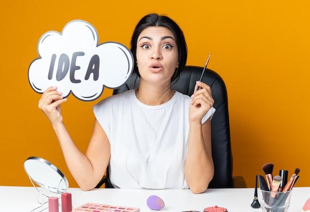 Une belle femme effrayée est assise à table avec des outils de maquillage tenant une bulle d'idée avec un pinceau de maquillage