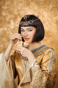 Belle femme égyptienne comme cléopâtre avec bouteille de parfum