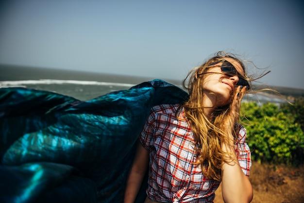 Belle femme élancée sur la roche de la mer avec un châle paréo