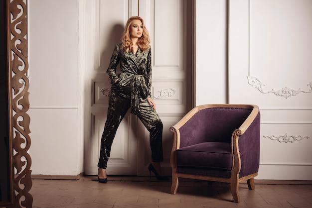 Belle femme élégante adulte debout près de fauteuil contre de grandes portes blanches