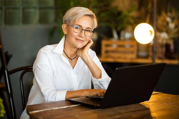 Belle femme élégante âgée dans des verres à la table avec un ordinateur portable