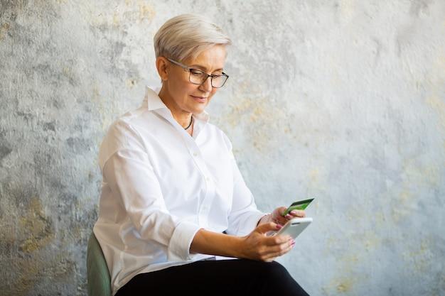 Belle femme élégante âgée dans des verres avec un téléphone mobile et une carte de crédit