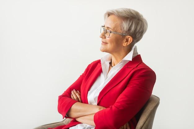 Belle femme élégante âgée dans une veste rouge avec des lunettes