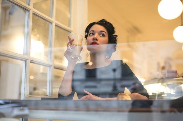 Belle femme élégante, assise dans un bar, buvant du chocolat chaud