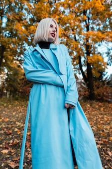 Belle femme élégante aux cheveux blonds courts dans un manteau bleu à la mode pose dans une forêt d'automne sur fond de feuillage d'automne jaune