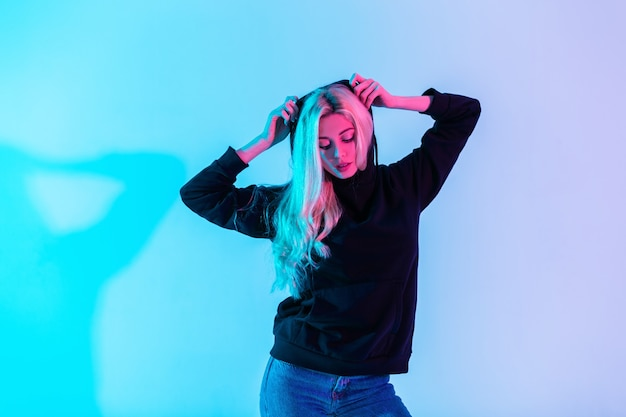 Belle femme élégante aux cheveux blonds dans un sweat à capuche noir à la mode portant une capuche en studio sur un fond rose néon coloré