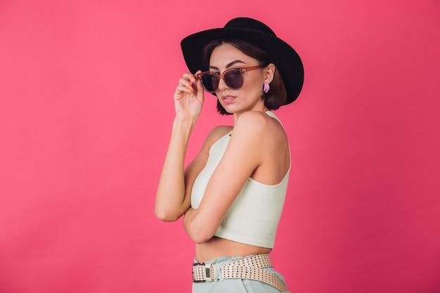 Belle femme élégante en chapeau et lunettes de soleil posant sur un mur rouge rose