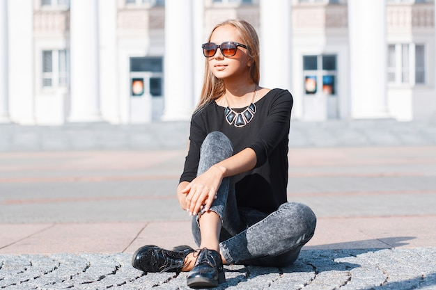 Belle femme élégante dans un jean tshirt noir et des chaussures assis sur le carreau