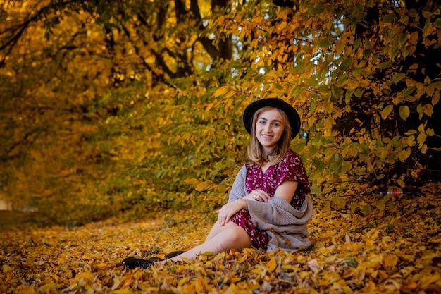 Belle femme élégante debout dans un parc à l'automne, concept d'automne.
