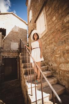 Belle femme élégante descendant les escaliers au vieux bâtiment en pierre