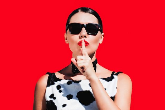 Belle femme élégante avec des lunettes de soleil et des lèvres peintes brillantes