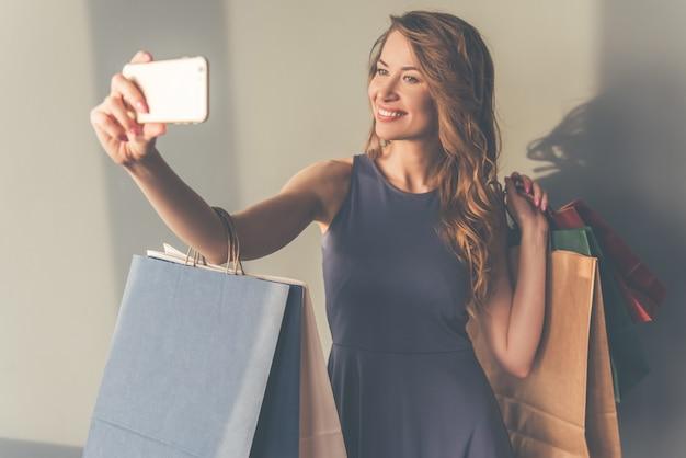 Belle femme élégante en robe de cocktail fait selfie