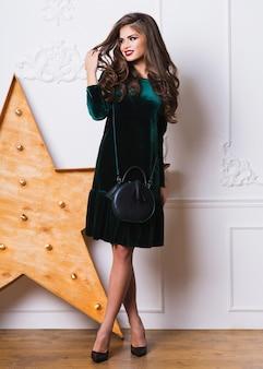 Belle femme en élégante robe de velours vert posant
