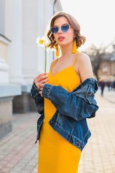 Belle femme élégante sexy en robe élégante jaune portant une veste en jean, tenue à la mode, tendance de la mode printemps-été, ensoleillé, lunettes de soleil bleues, mode de rue, style hipster, accessoires à la mode