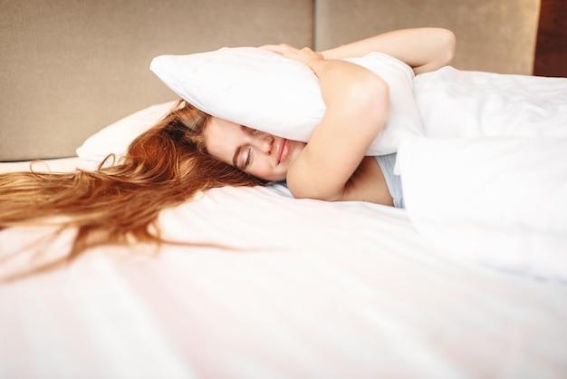 Belle femme embrasse l'oreiller, se réveillant. literie du matin à la maison, détente dans la chambre