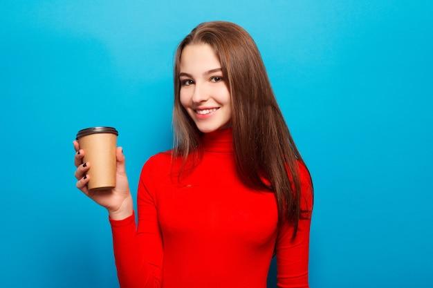 Belle femme émotionnelle heureuse en chemisier rouge sur fond de studio bleu buvant du café