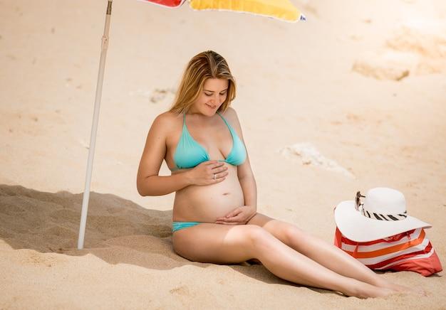 Belle femme enceinte en bikini assise sous un parasol et parlant à l'abdomen