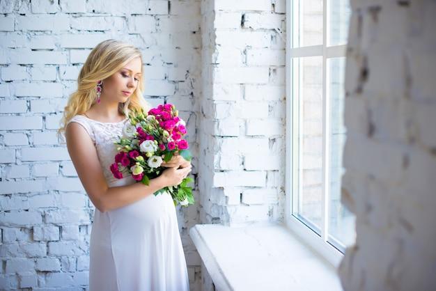 Une belle femme enceinte avec un bouquet de fleurs attendant la grossesse de bébé