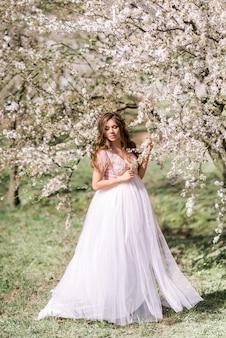 Belle femme enceinte dans une longue robe légère se promène dans un jardin de printemps fleuri.