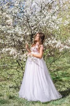 Belle femme enceinte dans une longue robe légère se promène dans un jardin de printemps en fleurs dans le jardin de printemps