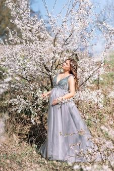 Belle femme enceinte dans une robe élégante dans un jardin de printemps en fleurs