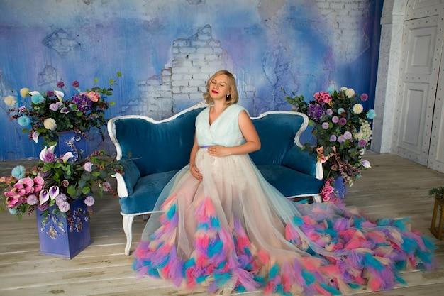 Belle femme enceinte est assise sur le canapé du loft studio parmi les fleurs, les yeux fermés