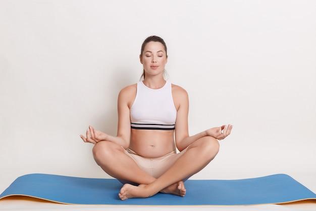 Belle femme enceinte faisant du yoga à la maison