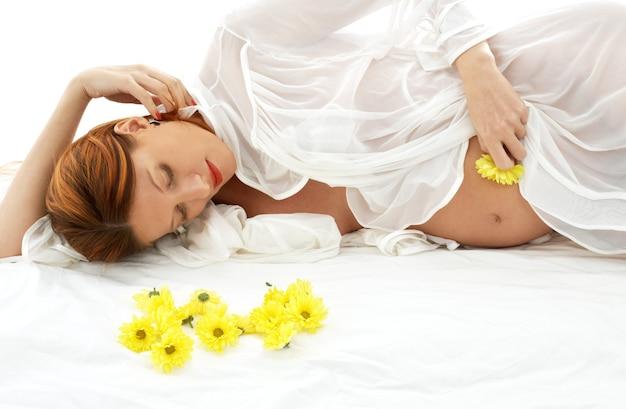 Belle femme enceinte avec des fleurs jaunes au lit