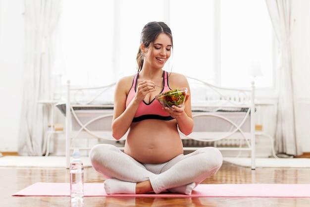 Belle femme enceinte mangeant une salade dans une pièce lumineuse