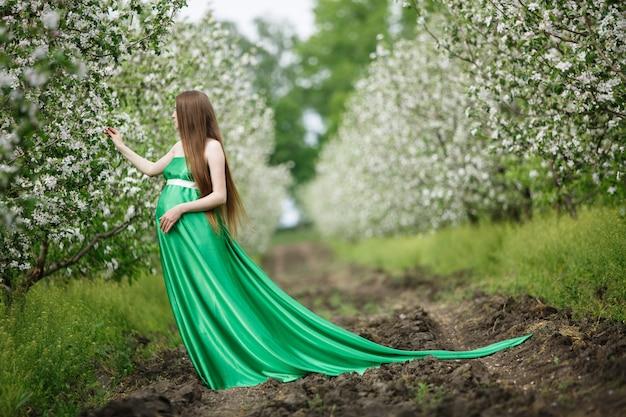 Belle femme enceinte marchant dans le jardin fleuri vert en journée ensoleillée. femme enceinte en robe longue se détendre et profiter dans le parc du printemps. fille enceinte en bonne santé à l'extérieur près des arbres. 9 mois