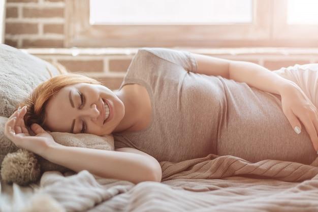 Belle femme enceinte portant sur le lit au repos