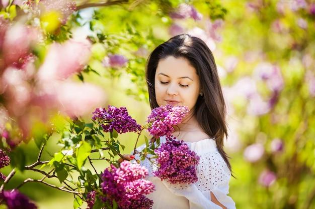 Belle femme enceinte profitant d'un jardin lilas