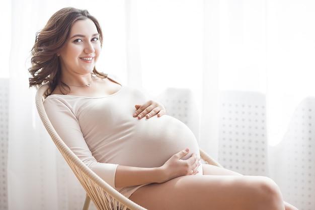 Belle femme enceinte sur scène neutre. image gros plan dans l'expectative.