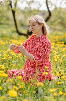 Belle femme enceinte se détendre dans le parc vêtue d'une robe rouge