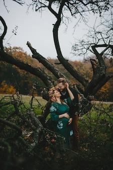 Belle femme enceinte et son homme s'embrassant dehors