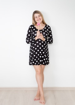 Belle femme enceinte souriante posant avec sucette